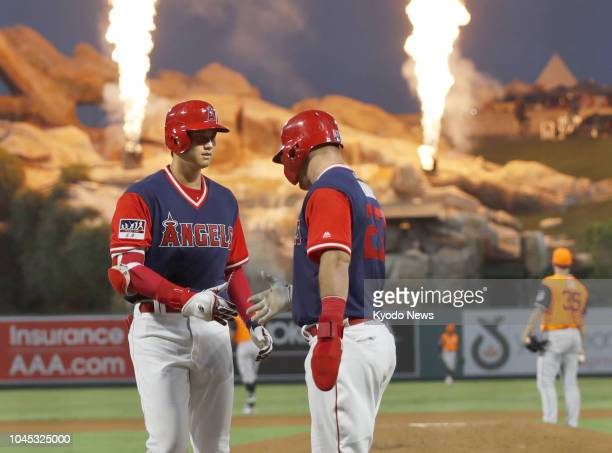 Shohei Ohtani and Mike Trout of the Los Angeles Angels shake hands after Ohtani hit a tworun home run in the fourth inning of a game against the...