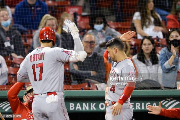 Shohei Ohtani celebrates with teammate José Iglesias of the Los Angeles Angels after hitting a solo home run in the sixth inning against the Boston...