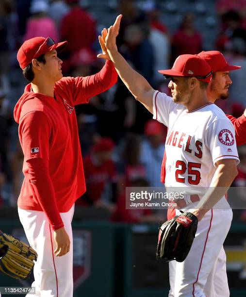 Shohei Ohtani gives Peter Bourjos of the Los Angeles Angels of Anaheim a high five after defeating the Texas Rangers at Angel Stadium of Anaheim on...