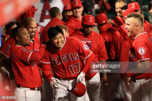 Shohei Ohtani is congratulated by Luis Valbuena and Mike Trout of the Los Angeles Angels of Anaheim in the dugout after hitting a threerun homerun...