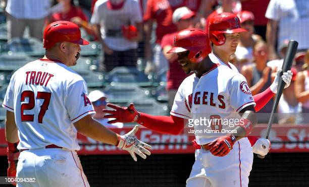 Shohei Ohtani looks on as Justin Upton shakes hands with Mike Trout of the Los Angeles Angels of Anaheim after hitting a two run home run in the...