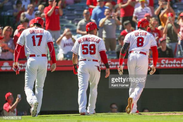 Shohei Ohtani Michael Hermosillo and Justin Upton of the Los Angeles Angels walk back to the dugout after Upton's homerun scoring 3 in the 3rd inning...