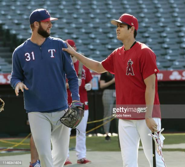 Shohei Ohtani of the Los Angeles Angels and Chris Martin of the Texas Rangers his former teammate with the Nippon Ham Fighters chat before a game at...