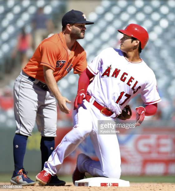 Shohei Ohtani of the Los Angeles Angels and Jose Altuve of the Houston Astros look at each other after Ohtani slides into second base during the...