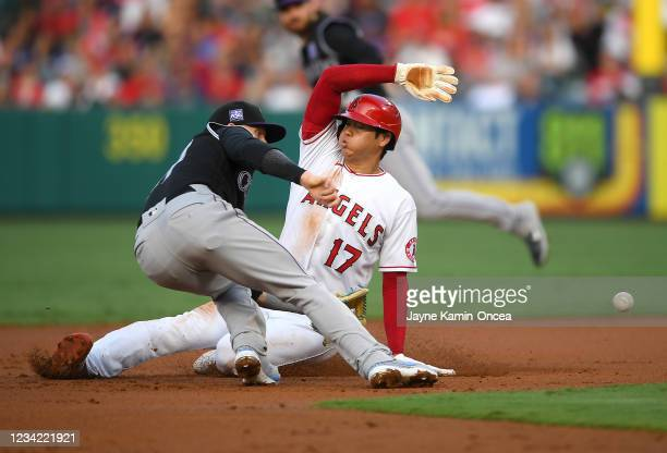 Shohei Ohtani of the Los Angeles Angels beats the tag by Trevor Story of the Colorado Rockies for a stolen base in the first inning of the game at...