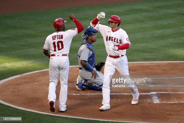 Shohei Ohtani of the Los Angeles Angels celebrates his home run with teammate Justin Upton of the Los Angeles Angels in the first inning against the...