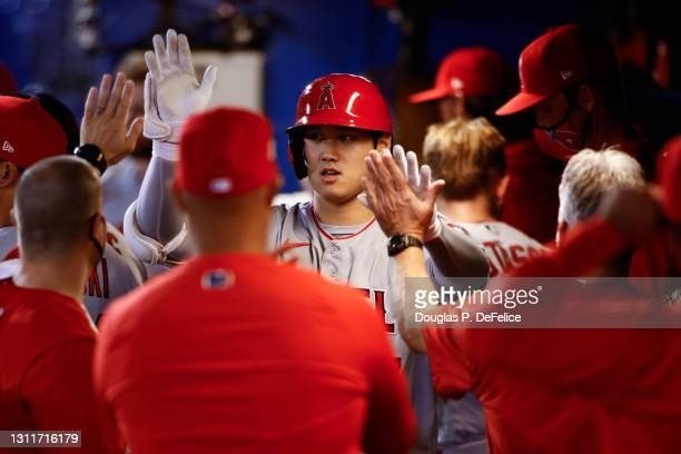 Shohei Ohtani of the Los Angeles Angels celebrates with his teammates in the dugout after hitting a solo home run to center field during the fifth...