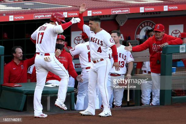 Shohei Ohtani of the Los Angeles Angels celebrates with Jose Iglesias of the Los Angeles Angels after hitting a home run in the first inning against...