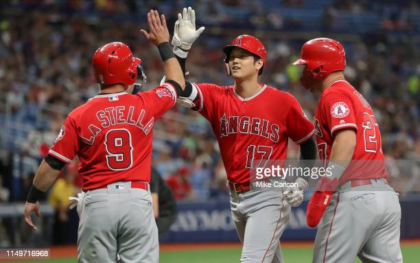 Shohei Ohtani of the Los Angeles Angels center is congratulated on his threerun home run by Tommy La Stella and Mike Trout in the first inning of a...