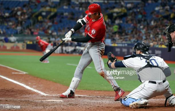 Shohei Ohtani of the Los Angeles Angels connects with a single in front of Mike Zunino of the Tampa Bay Rays in the seventh inning of a baseball game...
