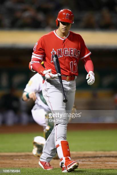 Shohei Ohtani of the Los Angeles Angels flips his bat in the air after being walked in the second inning against the Oakland Athletics at Oakland...