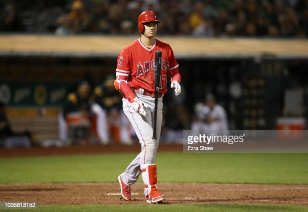 Shohei Ohtani of the Los Angeles Angels flips his bat in the air after being walked in the eighth inning against the Oakland Athletics at Oakland...