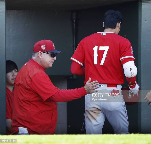 Shohei Ohtani of the Los Angeles Angels gets a pat from manager Mike Scioscia in the dugout after striking out in the eighth inning of a spring...