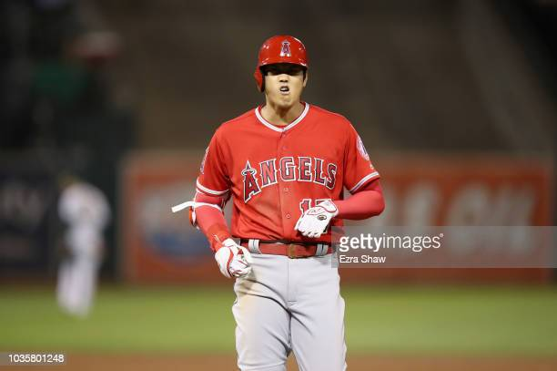 Shohei Ohtani of the Los Angeles Angels grimaces after he reached first base on a single in the sixth inning against the Oakland Athletics at Oakland...