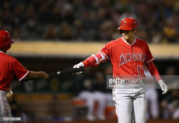 Shohei Ohtani of the Los Angeles Angels hands the batboy his bat after being walked in the second inning against the Oakland Athletics at Oakland...