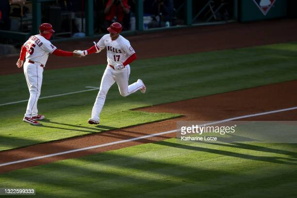 Shohei Ohtani of the Los Angeles Angels high-fives third base coach Brian Butterfield of the Los Angeles Angels after hitting an home run in the...