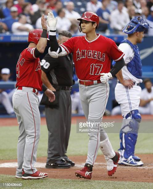 Shohei Ohtani of the Los Angeles Angels highfives Tommy La Stella after hitting a threerun home run in the second inning of a game against the...