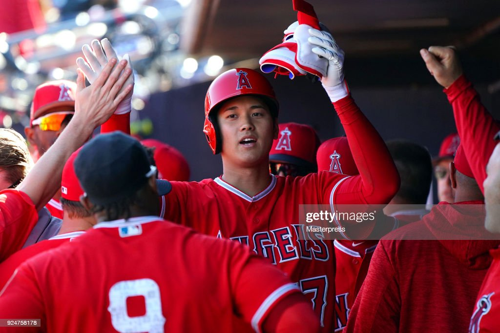 Shohei Ohtani of the Los Angeles Angels high-fives with teammates in the dugout after hitting an RBI single in the fifth inning during the game between Sand Diego Padres and Los Angeles Angels on February 26, 2018 in Peoria, Arizona.