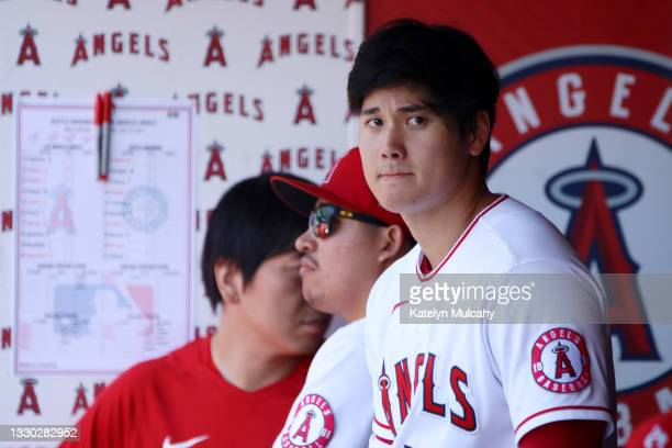 Shohei Ohtani of the Los Angeles Angels looks on from the dugout during the first inning Mariners at Angel Stadium of Anaheim on July 18, 2021 in...