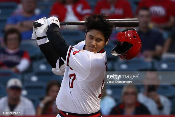 Shohei Ohtani of the Los Angeles Angels loses his helmet as he strikes out swinging in the first inning during the MLB game against the Chicago White...