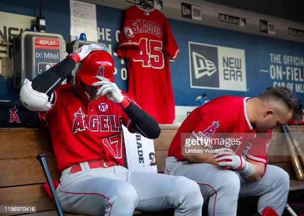 Shohei Ohtani of the Los Angeles Angels of Anaheim and Mike Trout, right prepare in the dugout as a Tyler Skaggs jersey hangs behind them before the...