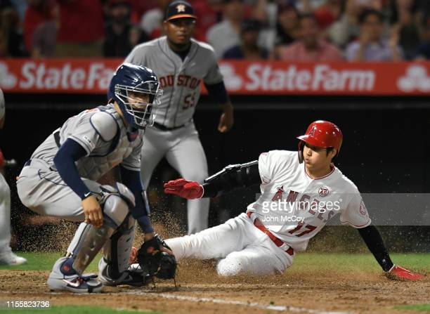 Shohei Ohtani of the Los Angeles Angels of Anaheim beats the throw to Robinson Chirinos of the Houston Astros at home plate to score a run on a...