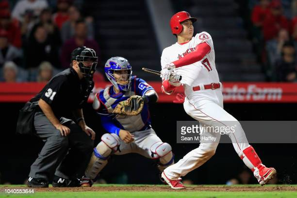 Shohei Ohtani of the Los Angeles Angels of Anaheim breaks his bat on an infield grounder as Robinson Chirinos of the Texas Rangers and umpire Pat...