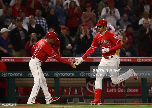 Shohei Ohtani of the Los Angeles Angels of Anaheim celebrates his solo homerun with third base coach Dino Ebel as Ohtani rounds third base in the...