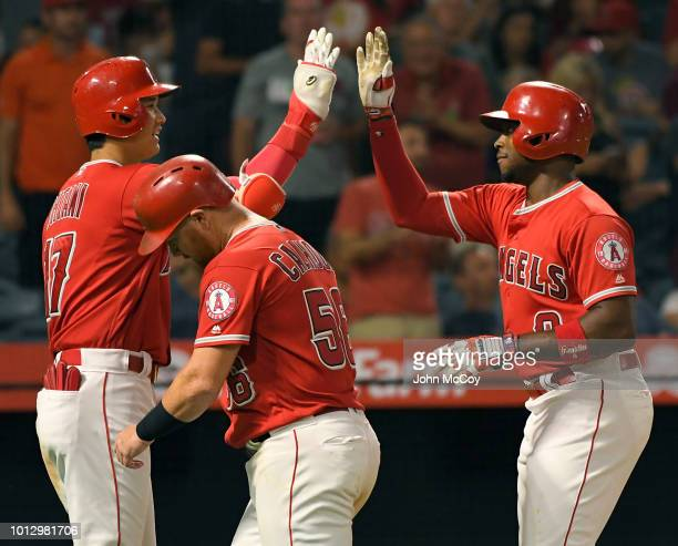 Shohei Ohtani of the Los Angeles Angels of Anaheim congratulates Justin Upton on his two run home run that drove in Kole Calhoun in the sixth inning...