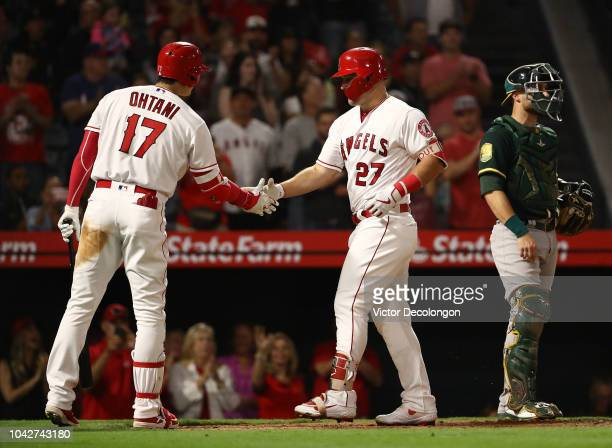 Shohei Ohtani of the Los Angeles Angels of Anaheim congratulates teammate Mike Trout at home plate after Trout hit a tworun homerun as catcher...