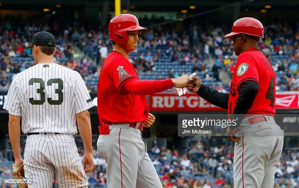 Shohei Ohtani of the Los Angeles Angels of Anaheim fist bumps first base coach Alfredo Griffin after drawing a walk in the ninth inning as Greg Bird...