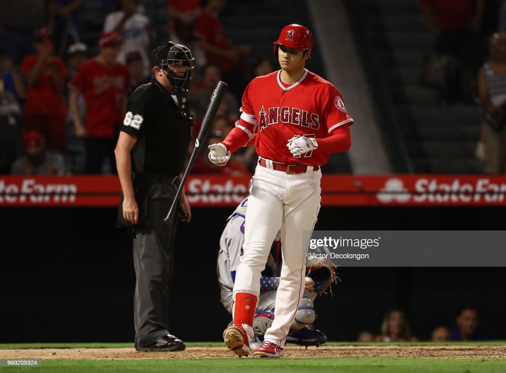 Shohei Ohtani #17 of the Los Angeles Angels of Anaheim flips his bat after drawing a walk in the ninth during the MLB against the Los Angeles Dodgers at Angel Stadium on July 6, 2018 in Anaheim, California. The Angels defeated the Dodgers 3-2.