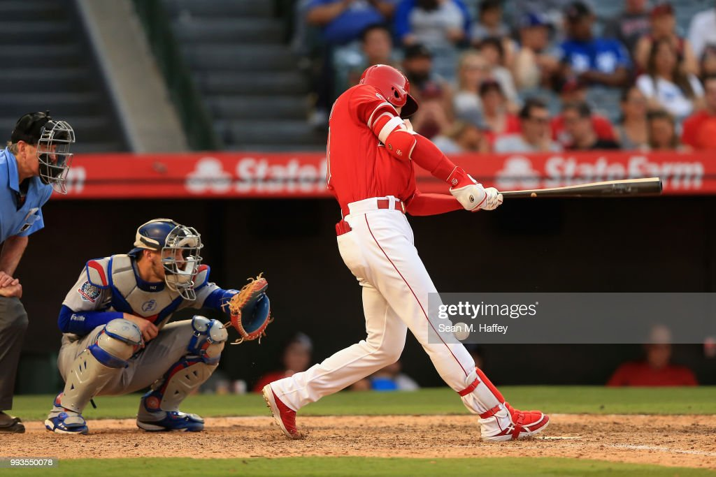 Shohei Ohtani #17 of the Los Angeles Angels of Anaheim fouls a ball off of his knee as Yasmani Grandal #9 of the Los Angeles Dodgers and umpire Mike Winters look on during the ninth inning of a game at Angel Stadium on July 7, 2018 in Anaheim, California.