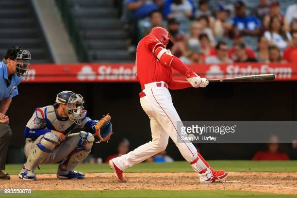Shohei Ohtani of the Los Angeles Angels of Anaheim fouls a ball off of his knee as Yasmani Grandal of the Los Angeles Dodgers and umpire Mike Winters...