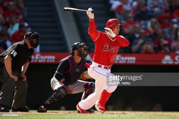 Shohei Ohtani of the Los Angeles Angels of Anaheim grounds out during the eighth inning of a game as Yan Gomes of the Cleveland Indians looks on at...