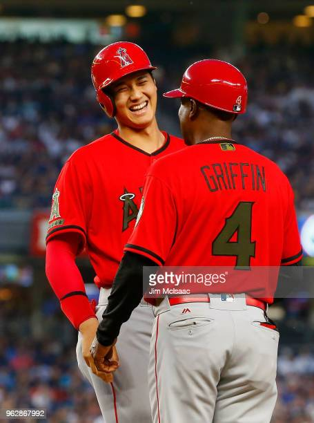 Shohei Ohtani of the Los Angeles Angels of Anaheim has a laugh with first base coach Alfredo Griffin after drawing a bases loaded walk during the...