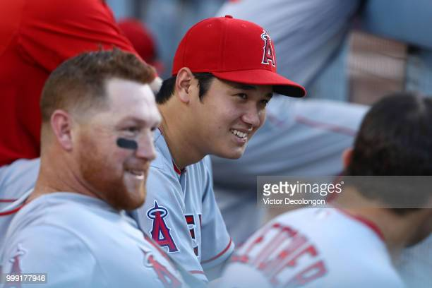 Shohei Ohtani of the Los Angeles Angels of Anaheim has a laugh with teammate Kole Calhoun in the dugout during the ninth inning of the MLB game...