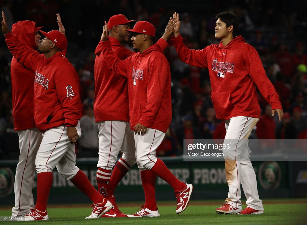Shohei Ohtani #17 of the Los Angeles Angels of Anaheim, (R) high-fives with teammates after their 13-9 win over the Oakland Athletics at Angel Stadium on April 6, 2018 in Anaheim, California.