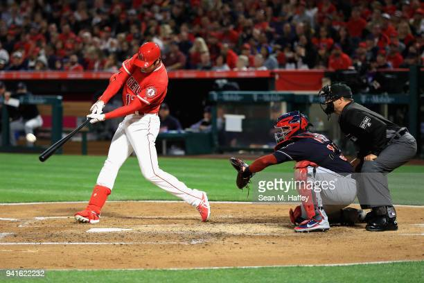 Shohei Ohtani of the Los Angeles Angels of Anaheim hits a threerun homerun during the first inning of a game as Roberto Perez of the Cleveland...