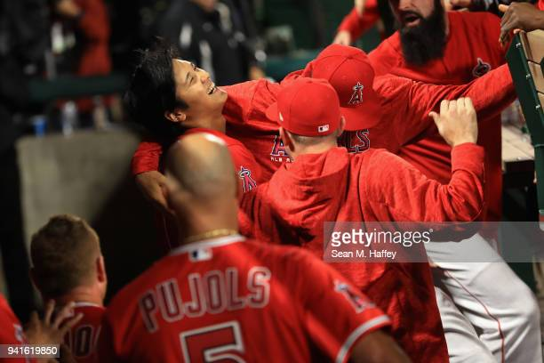 Shohei Ohtani of the Los Angeles Angels of Anaheim is congratulated by teammates in the dugout after hitting a threerun homerun during the first...