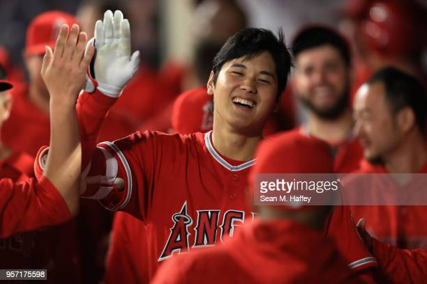 Shohei Ohtani of the Los Angeles Angels of Anaheim is congratulated in the dugout after hitting a solo homerun during the seventh inning of a game...