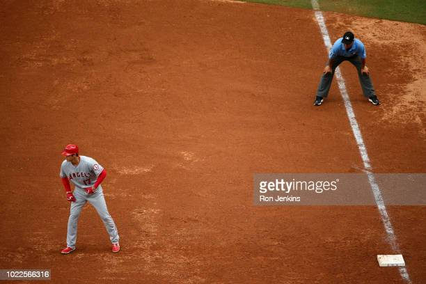 Shohei Ohtani of the Los Angeles Angels of Anaheim leads off first base as umpire Vic Carapazza stands nearby against the Texas Rangers during the...