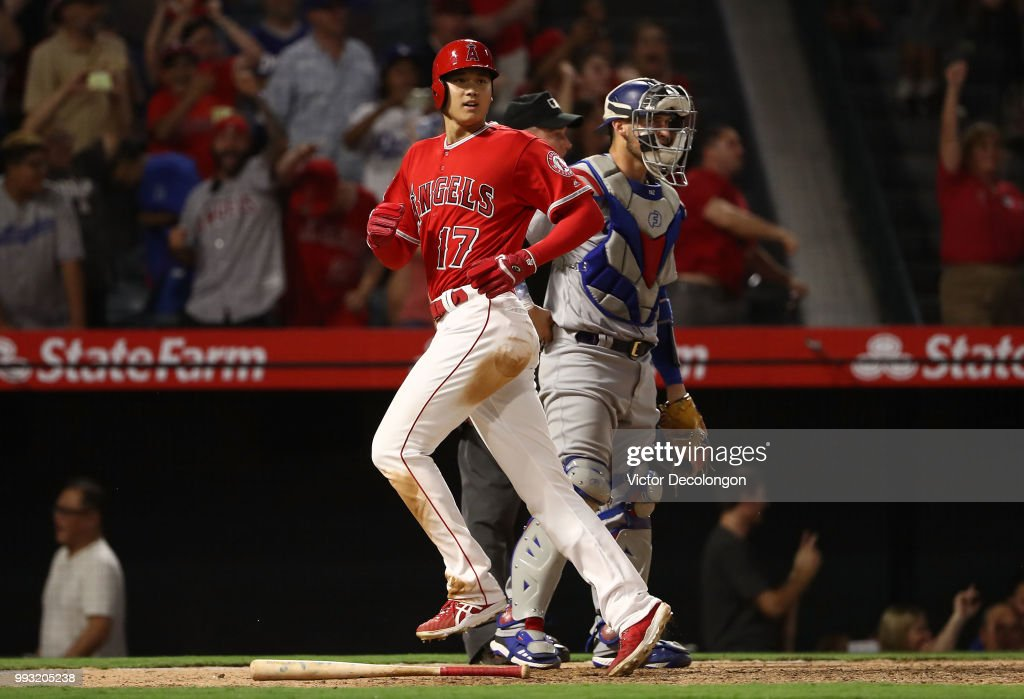 Shohei Ohtani #17 of the Los Angeles Angels of Anaheim looks toward first base to teammate David Fletcher #6 (not in photo) as Ohtani crosses home plate to score while catcher Yasmani Grandal #9 of the Los Angeles Dodgers look on in the ninth during the MLB at Angel Stadium on July 6, 2018 in Anaheim, California. The Angels defeated the Dodgers 3-2.