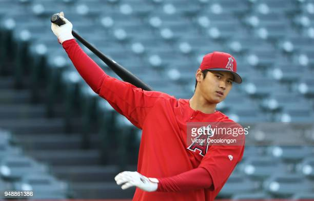 Shohei Ohtani of the Los Angeles Angels of Anaheim practices his swing behind the batting cage during batting practice prior to the MLB game against...