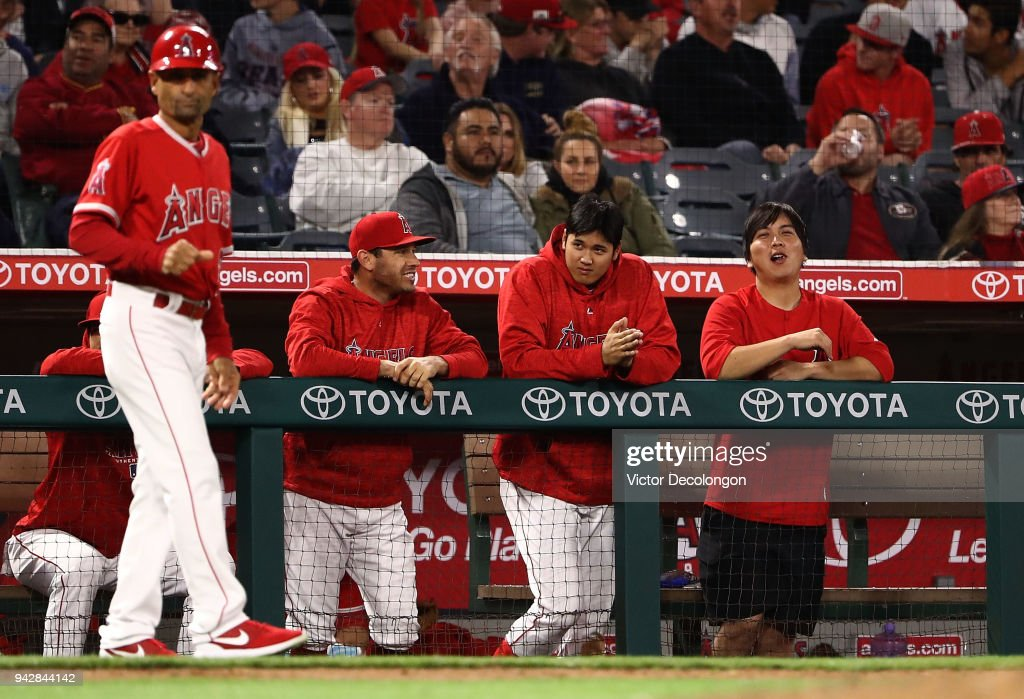 Shohei Ohtani #17 of the Los Angeles Angels of Anaheim, second from right, puts his hands together to urge on teammate Martin Maldonado #12 during Maldonado's at-bat (not in photo) in the seventh inning of the MLB game against the Oakland Athletics at Angel Stadium on April 6, 2018 in Anaheim, California.