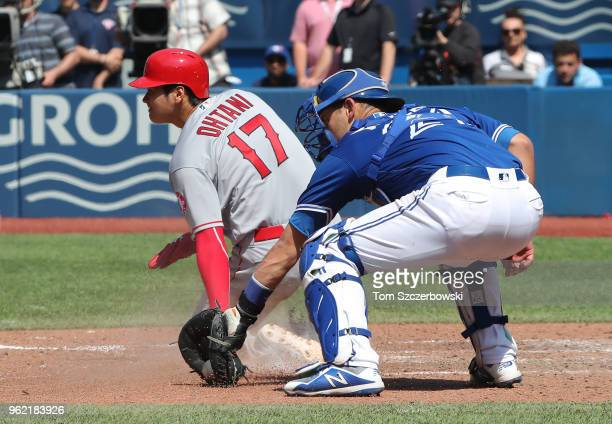 Shohei Ohtani of the Los Angeles Angels of Anaheim slides across home plate to score a run in the ninth inning during MLB game action as Luke Maile...