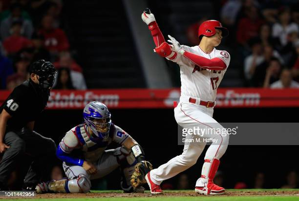 Shohei Ohtani of the Los Angeles Angels of Anaheim strikes out during the first inning as Robinson Chirinos of the Texas Rangers and umpire Roberto...