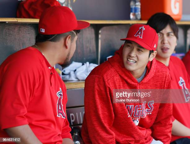 Shohei Ohtani of the Los Angeles Angels of Anaheim talks with a teammate during the sixth inning of a game against the Detroit Tigers at Comerica...
