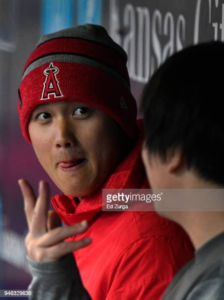 Shohei Ohtani of the Los Angeles Angels of Anaheim talks with his interpreter as they sit in the dugout in the fourth inning during a game against...