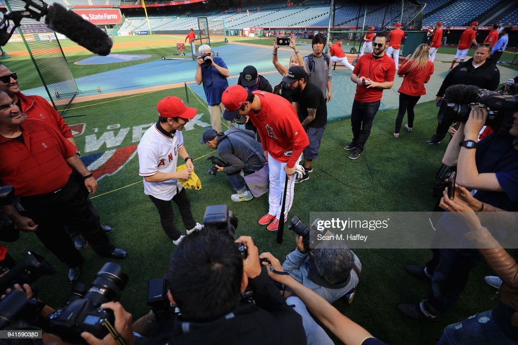 Shohei Ohtani #17 of the Los Angeles Angels of Anaheim talks with professional race driver Takuma Sato of Japan prior to a game against the Cleveland Indians at Angel Stadium on April 3, 2018 in Anaheim, California.